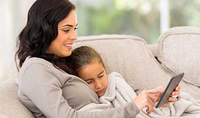 mother and child on couch using smartphone
